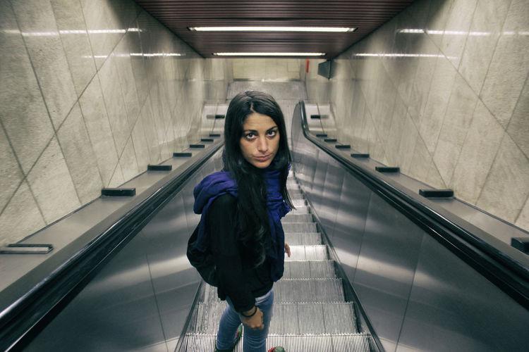 High Angle Portrait Of Woman Standing On Escalator