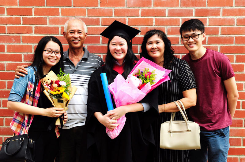Portrait of family standing against brick wall during convocation