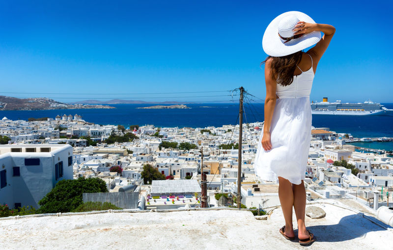 Woman in white dress stands over Mykonos town and enjoys the view, Greece Above Aegean Sea Behind Blue Cruise Ship Dress Elegant Fashion Girl Greece Greek Hat Holiday Island Model Mykonos Summer Travel Destinations Vacation View View From Above White Windmill Woman Young