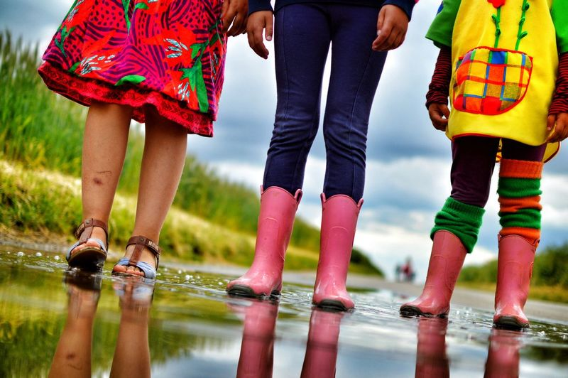 Low section of children standing on puddle during rainy season