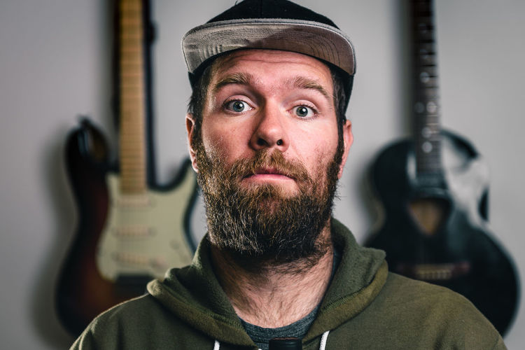 Young handsome man bearded hipster with beard and moustache portrait. Modern, casual looking, blue eyes musician guy with a hat and electric and acoustic guitars in the background. Acoustic Hat Adult Beard Craft Electricity  Guitars Headshot Hippy Hipster Hipster Man Indoors  Looking At Camera Mid Adult Mid Adult Men Music Man Musitian One Person Portrait Real People Repairman Standing Fresh On Market 2018