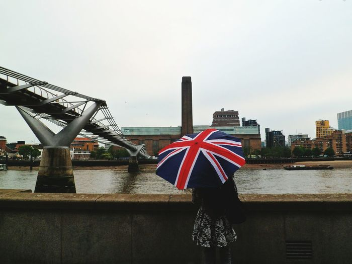 Woman with umbrella against river