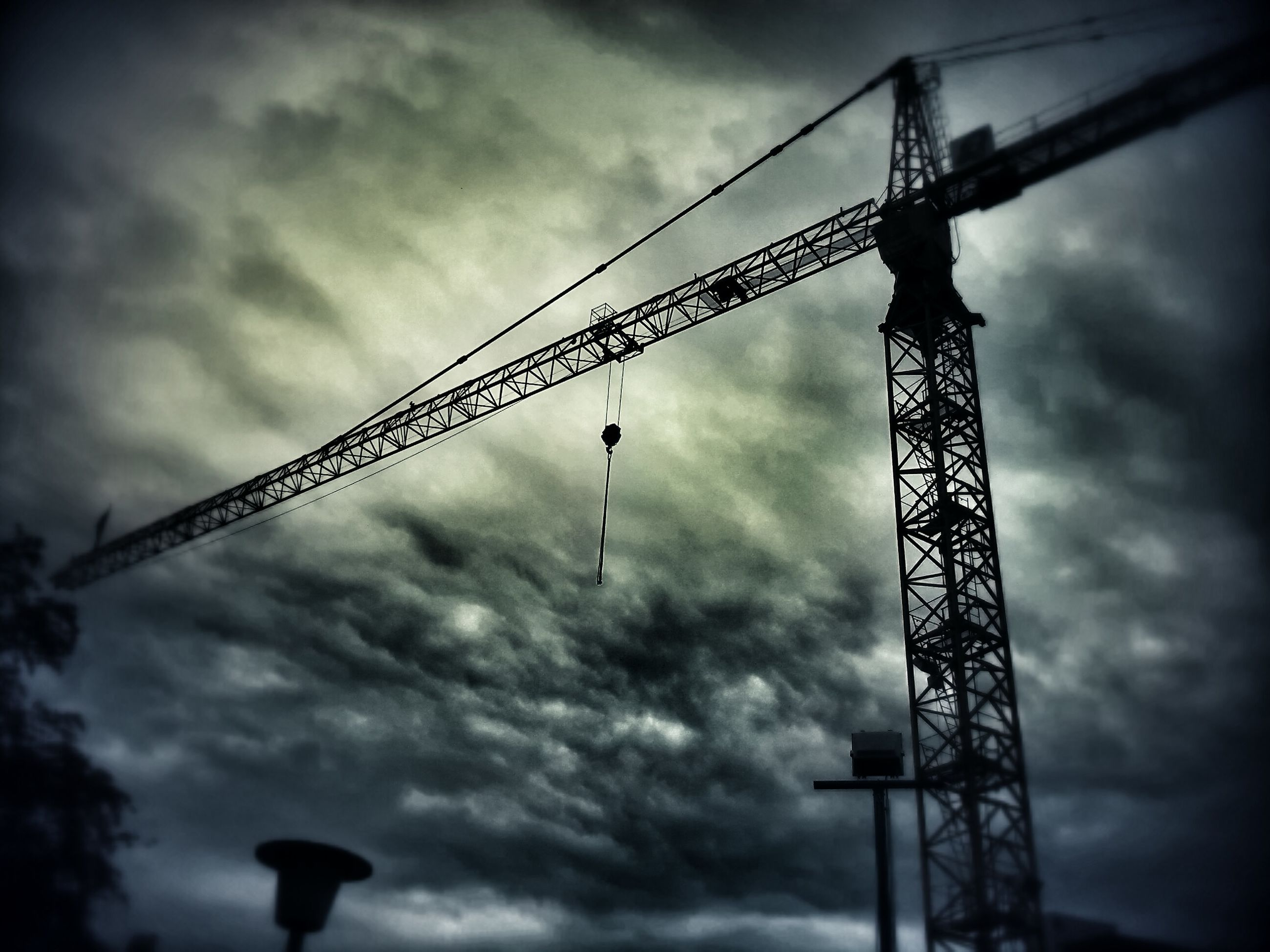 low angle view, sky, cloud - sky, cloudy, silhouette, cloud, metal, crane - construction machinery, overcast, crane, weather, connection, built structure, construction site, development, metallic, dusk, outdoors, no people, day