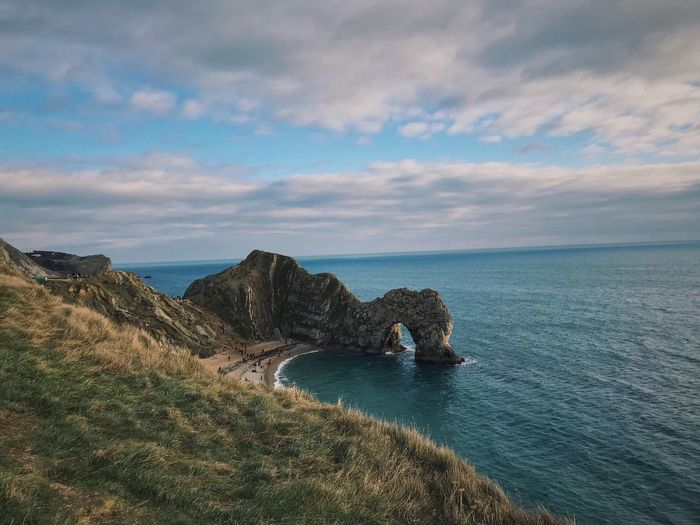 Durdle door 😮 Sea Nature Scenics Beauty In Nature Water Sky Tranquil Scene Horizon Over Water Tranquility Rock Formation Idyllic Rock - Object Cloud - Sky No People Physical Geography Cliff Outdoors Day Grass Durdle Door