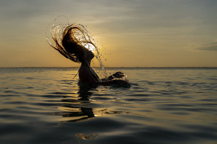 View of swimming in sea against sunset sky