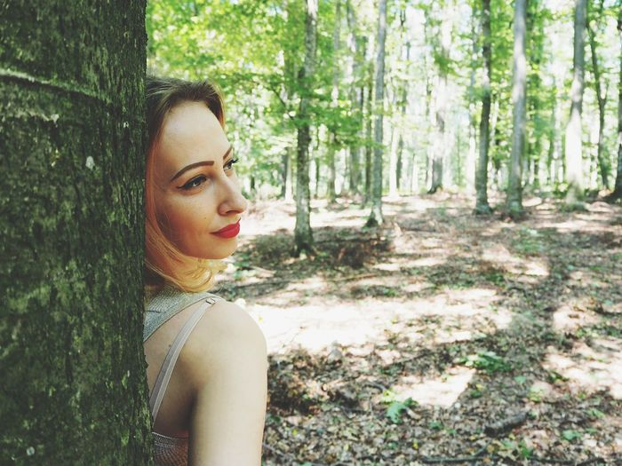 Thoughtful Woman Looking Away While Standing Against Tree At Forest