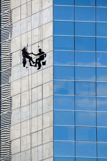 Reflection of people on swimming pool against building