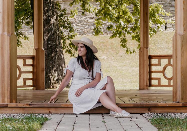 Woman wearing hat sitting on wood