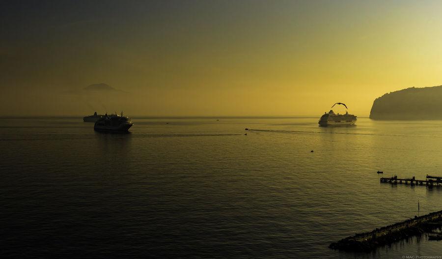 Cruise ships sailing in sea at sunset