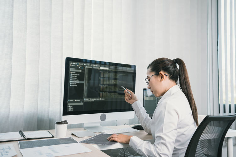 Side view of woman using laptop on table