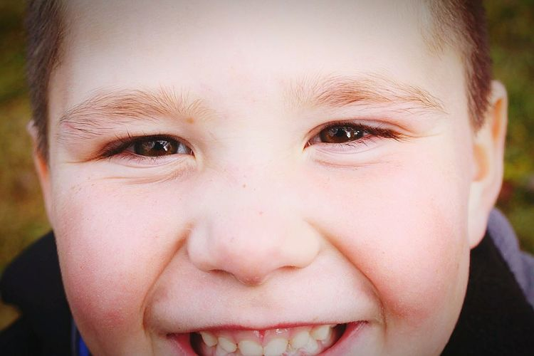 Close-Up Portrait Of Cheerful Boy