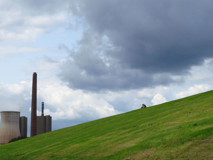 Low angle view of friends sitting on hill by cooling tower against cloudy sky