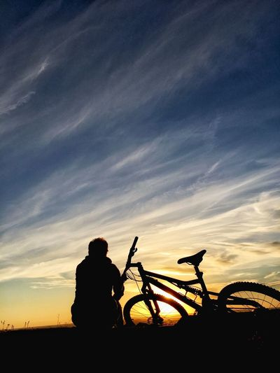 Silhouette Man With Bicycle Against Sky During Sunset