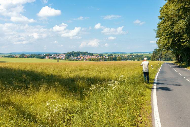 rear view of person on road amidst field against sky Baum Beauty In Nature Cloud - Sky Day Environment Field Grass Growth Juni Land Landscape Lifestyles Nature One Person Outdoors Plant Real People Rear View Road Sky Sunlight Transportation Tree Redefining Menswear