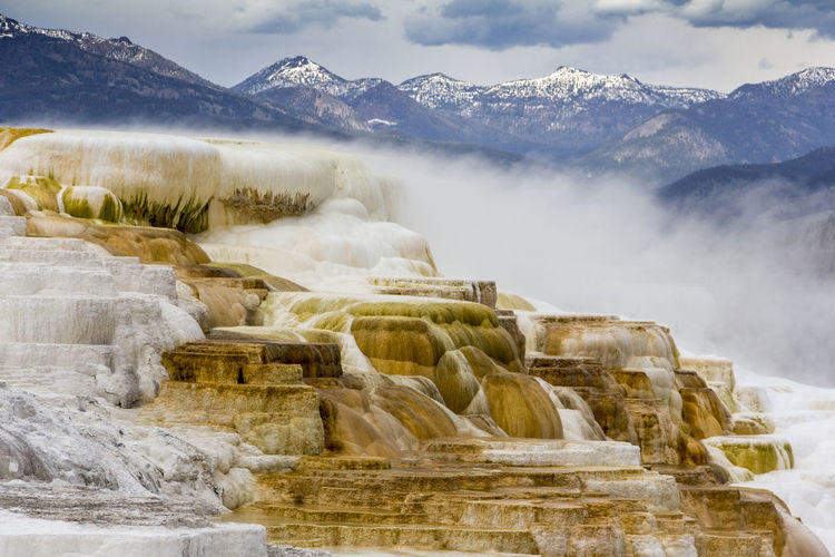 Scenic view of travertine pool against mountains at mammoth hot springs
