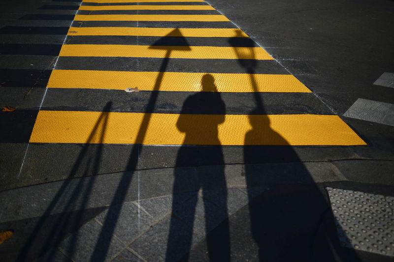 Shadows of people on yellow zebra crossing in city