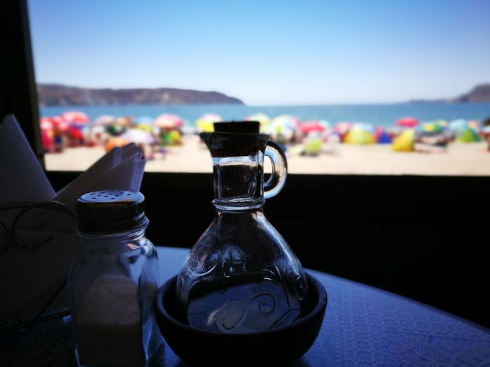 Close-up of salt shaker and jar on table at beach