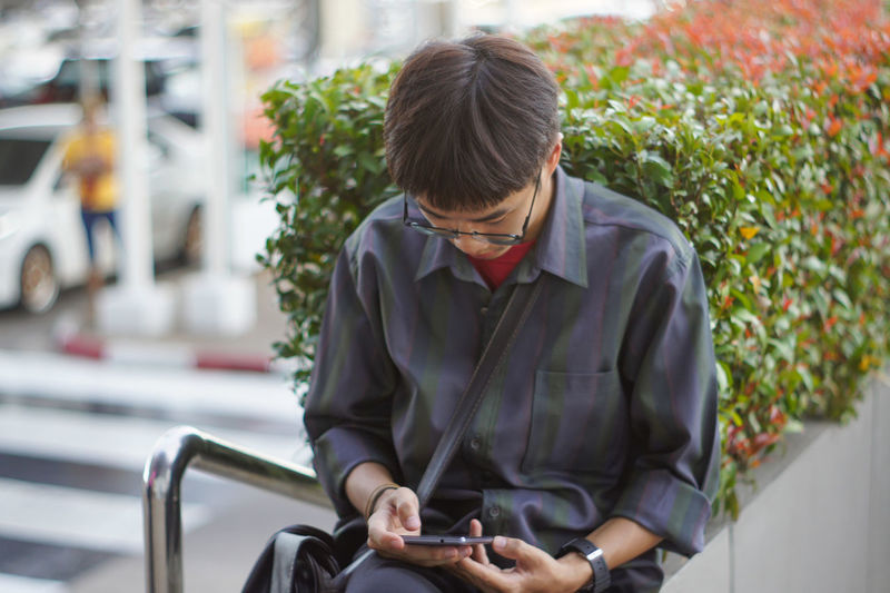 Man talking using mobile phone while sitting outdoors