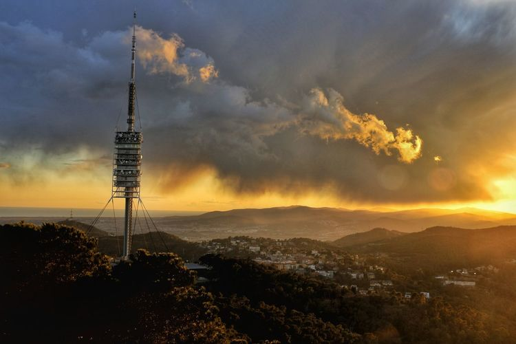Lookout Tower On Landscape Against Cloudy Sky During Sunset