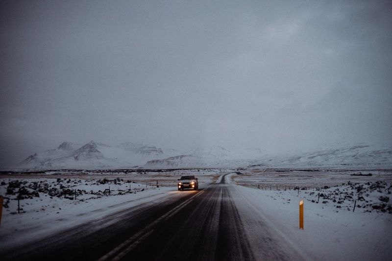 Cars on road against sky during winter