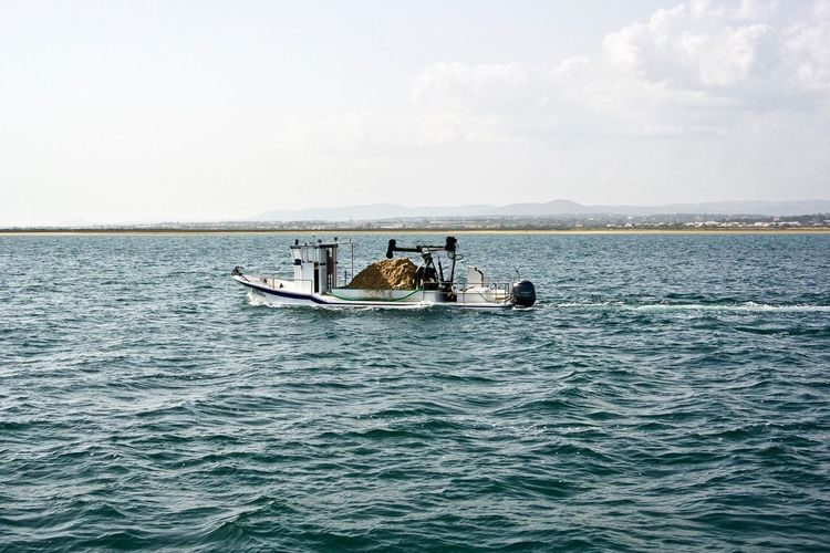 This boat is hauling sand to an island that is entirely made of sand. Construction Delivery Island Life Transport Transportation Boat Building Culatra Hauling Idyllic Island Delivery Mode Of Transportation Nautical Vessel Sand Transport Boat Transportation