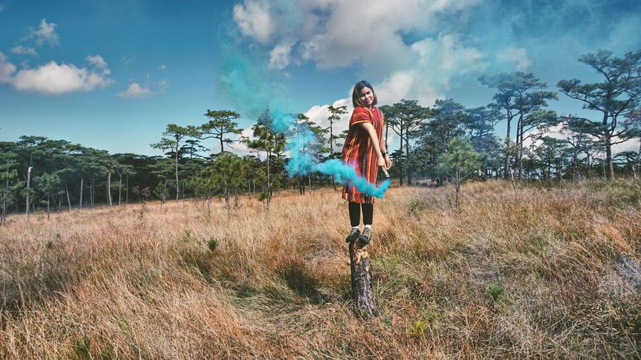 Woman Holding Distress Flare While Standing On Wooden Post