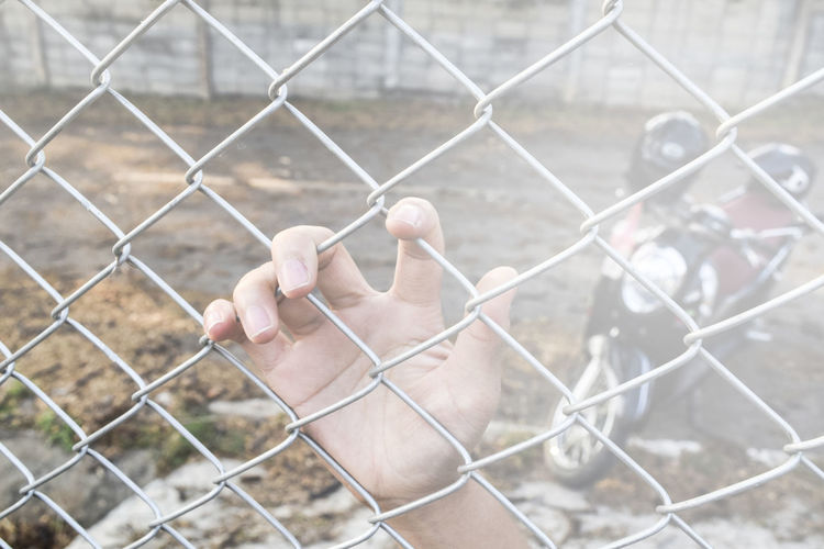 Adults Only Barbed Wire Chainlink Chainlink Fence Close-up Day Exclusion Fence Focus On Foreground Human Body Part Human Finger Human Hand Metal One Man Only One Person Only Men Outdoors People Prison Prisoner Protection Real People Safety Security Separation
