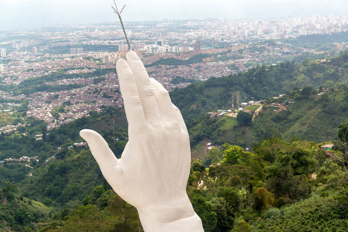 View of the hand of the El Santisimo statue in Floridablanca, Colombia with Bucaramanga visible in the background Bucaramanga Building Catholic Cerro Christ Christianity City Cloud Clouds Colombia Ecoparque Elsantisimo Floridablanca Jesus Landmark Park Religion Santander Santisimo Sculpture Statue Structure Urban View White
