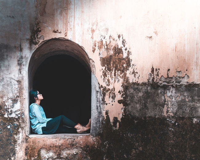 Man sitting on old wall