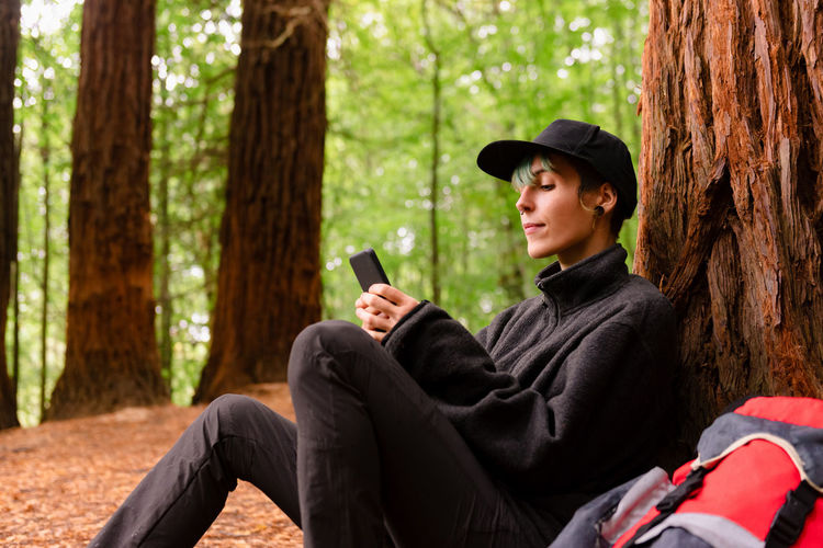 Young man using mobile phone while sitting in forest