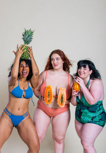 Portrait of smiling women holding fruits standing at home