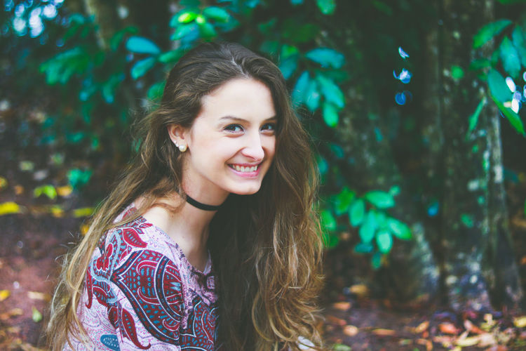 Beautiful Woman Close-up Day Focus On Foreground Forest Happiness Leisure Activity Lifestyles Long Hair Looking At Camera Nature One Person Outdoors Portrait Real People Smiling Standing Toothy Smile Tree Young Adult Young Women