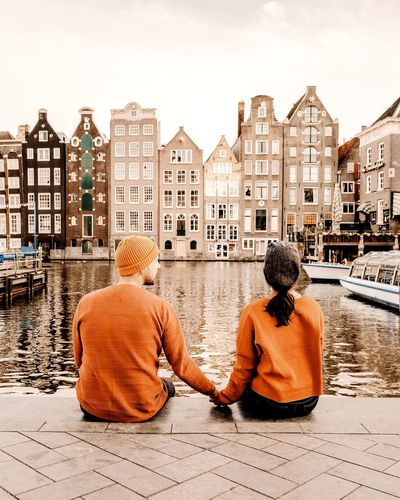 Rear view of couple holding hands while sitting by river against buildings in city