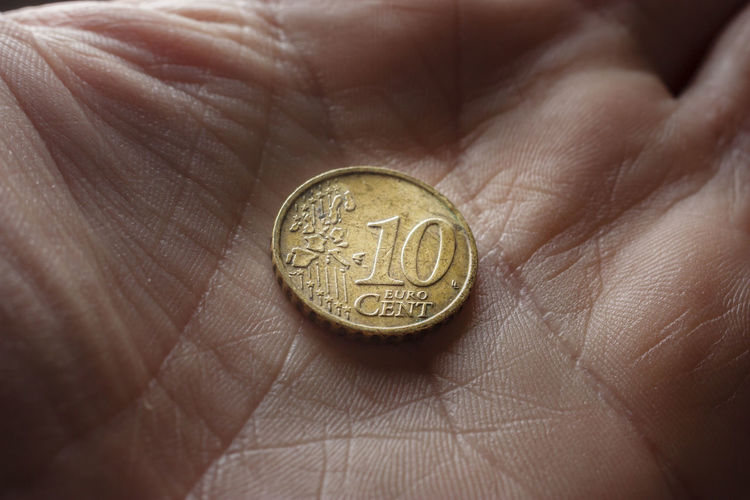Close-up of a hand holding coin