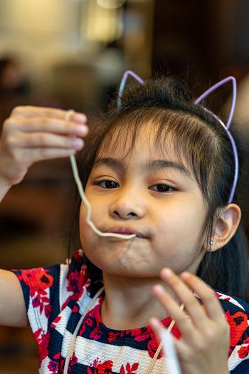 Cute girl eating noodles