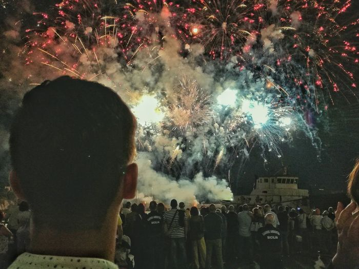 Rear view of people watching firework display at night