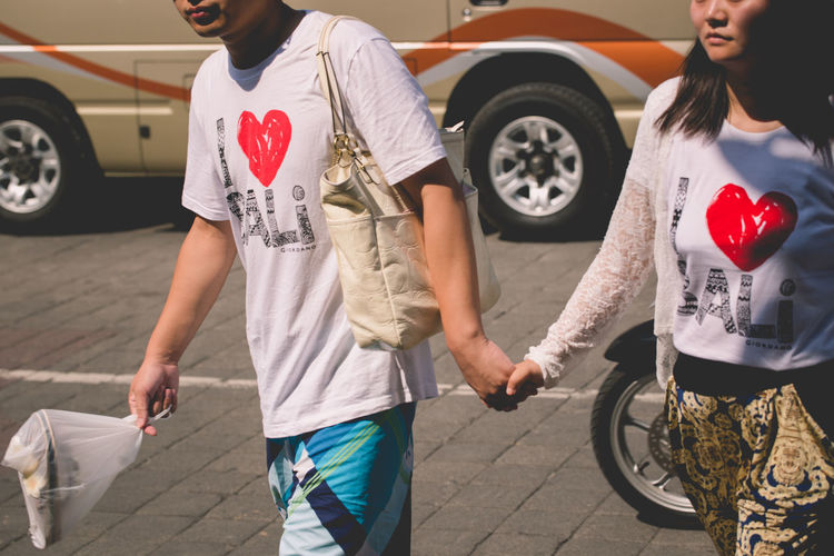 """Matching """"I love Bali"""" shirts Casual Clothing Day Holding Hands I Love BALI Leisure Activity Lifestyles Love Outdoors Tourists Walking Together The Street Photographer - 2018 EyeEm Awards The Traveler - 2018 EyeEm Awards Human Connection Streetwise Photography"""