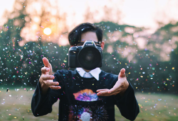 Man Throwing Camera Amidst Confetti