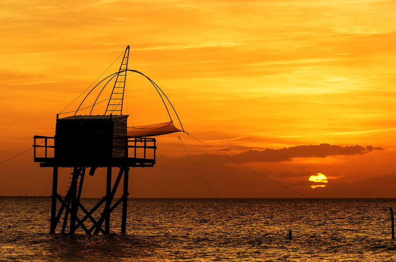 Sunset sur le carrelet Sunset Orange Color Water Silhouette Sea Beach Sand No People Sky Horizon Over Water Salt - Mineral Outdoors Tranquility Seascape Photography Beauty In Nature Clear Sky Fisherman Cabins Sunlight Landscape Connected By Travel
