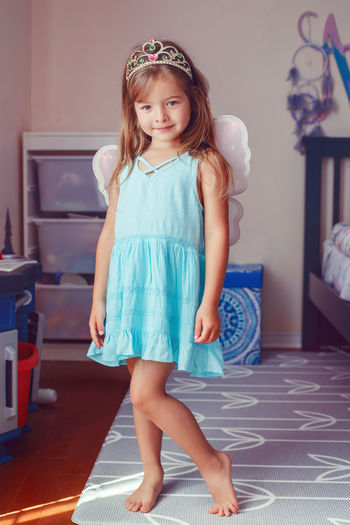 Portrait of a girl in fairy costume standing against wall on floor at home