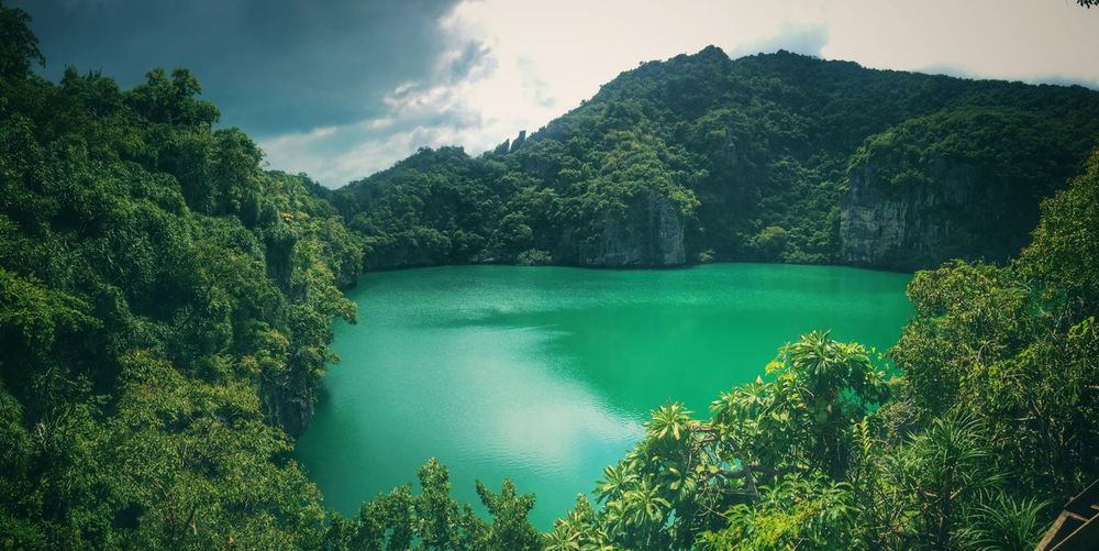 Scenic view of emerald green lake with mountains against sky - thailand