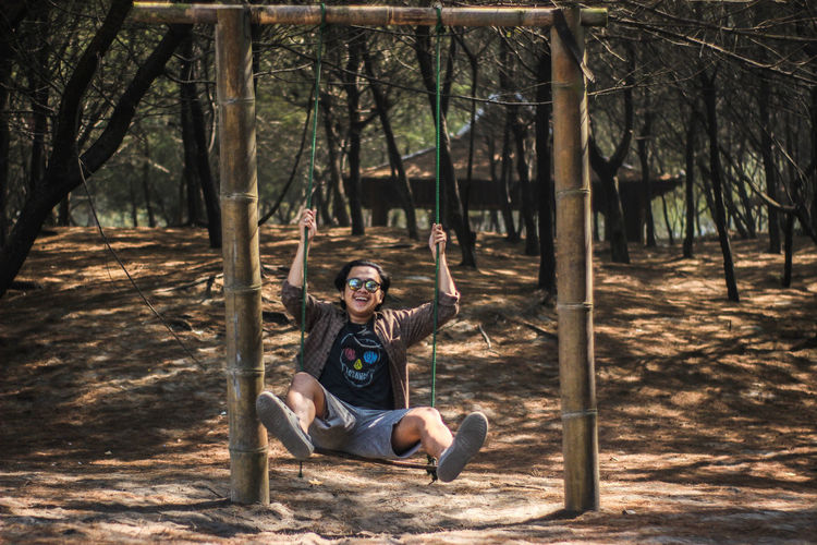 Portrait of young man sitting playing on swing