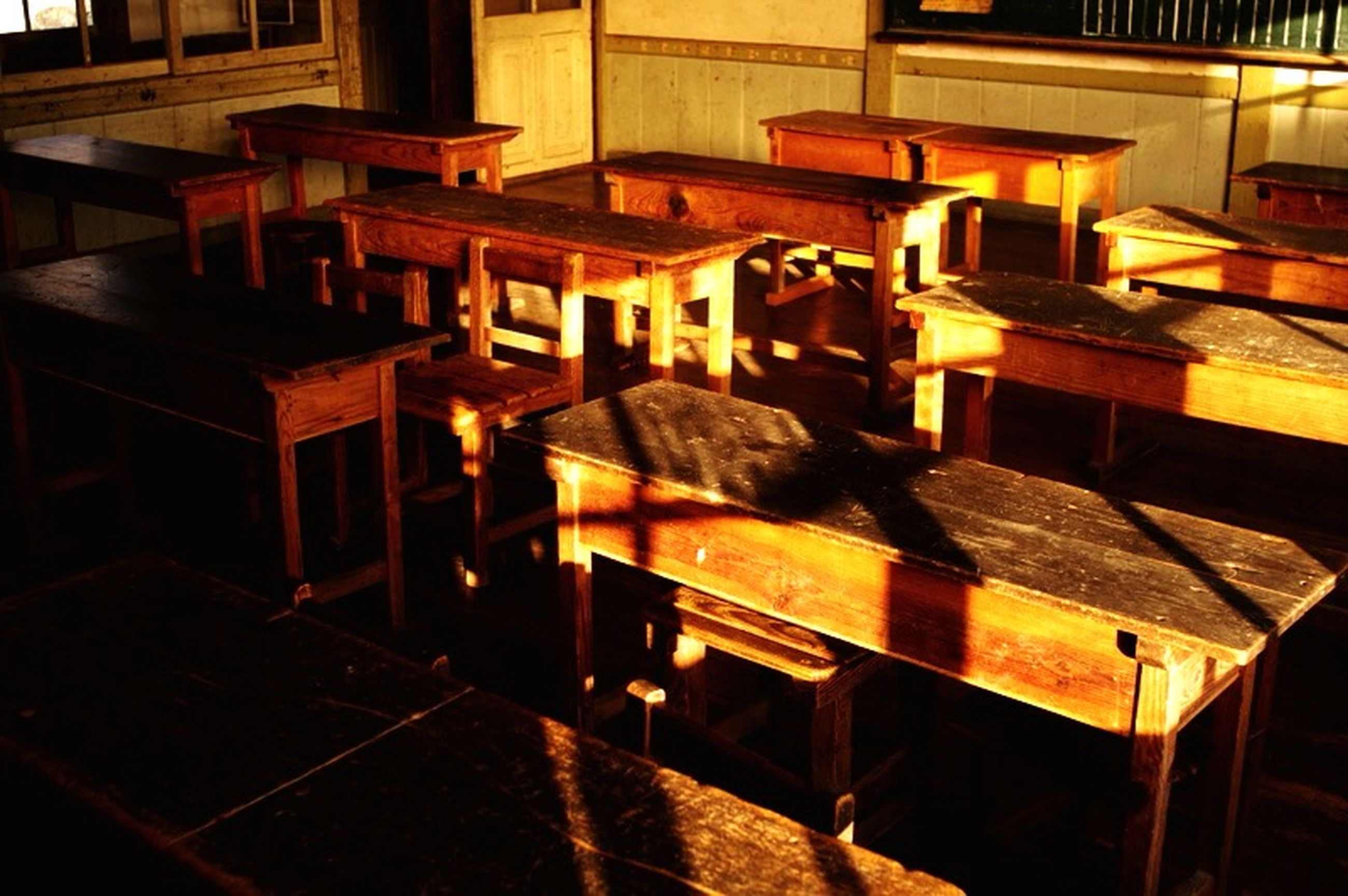 indoors, chair, table, absence, empty, illuminated, in a row, furniture, arrangement, large group of objects, restaurant, seat, no people, night, wood - material, shelf, stack, order, high angle view, still life