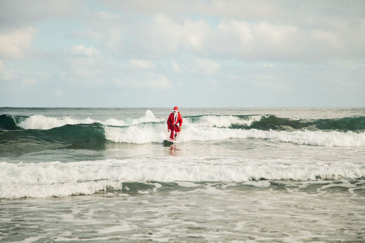 Man wearing santa costume surfing on sea against sky