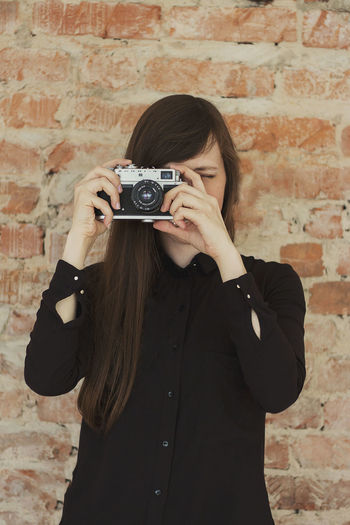Girl with a camera. the photographer takes a shot. film camera. girl photographer looking