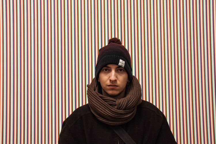 Portrait of hipster man wearing warm clothing against patterned wall