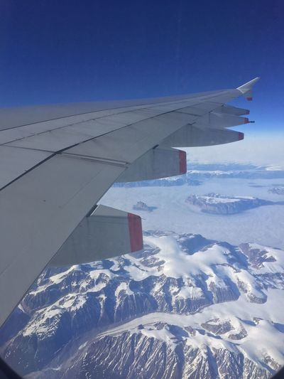 Airplane flying over snow covered landscape