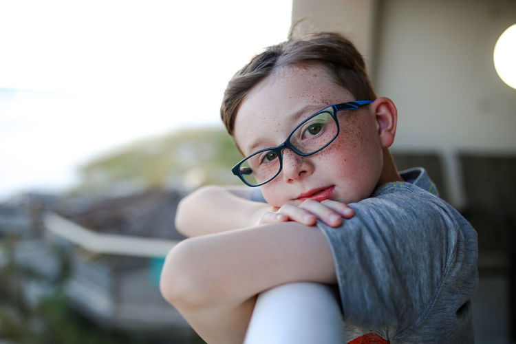 Boy wearing glasses while on the balcony at the beach Looking At Camera Eyeglasses Portrait Wearing Eyeglasses Wearing Glasses Balcony View Beach Boy Real People Innocence Focus On Foreground Childhood Child Glasses Eyeglasses  One Person Portrait Freckles Freckleseverywhere