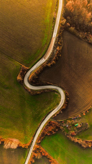 High angle view of winding road on agricultural landscape