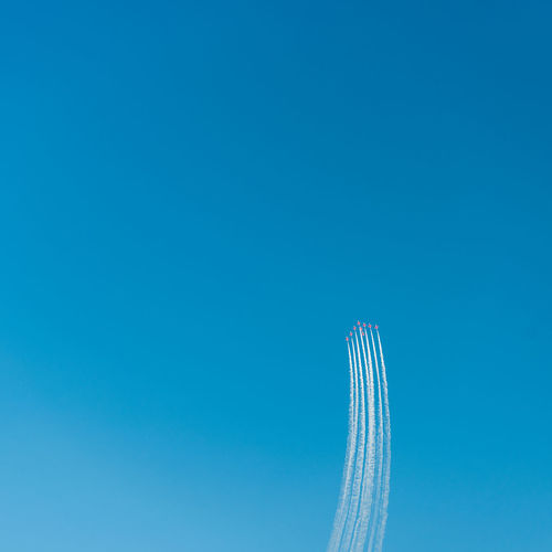 Low angle view of fighter planes flying against clear blue sky